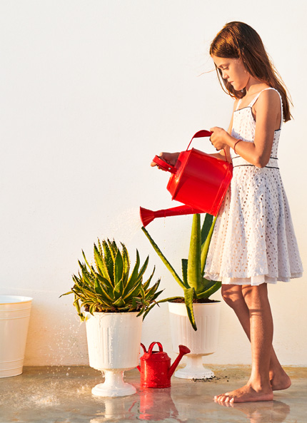 A young girl holding a red watering can and watering some greenery in a white plant pot.
