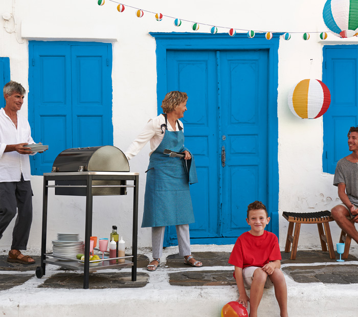 A Mother grilling in an outdoor space in front of a grill for her nearby family- a Father, a teenage boy and a young boy.