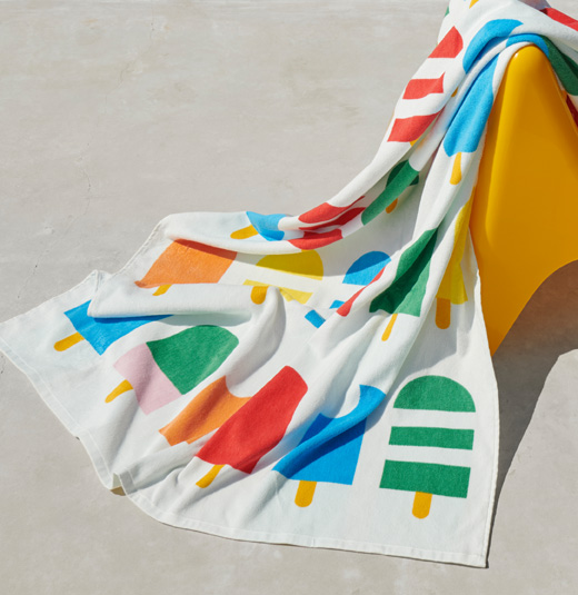 A white beach towel with multicolored ice creams draped over a yellow chair.