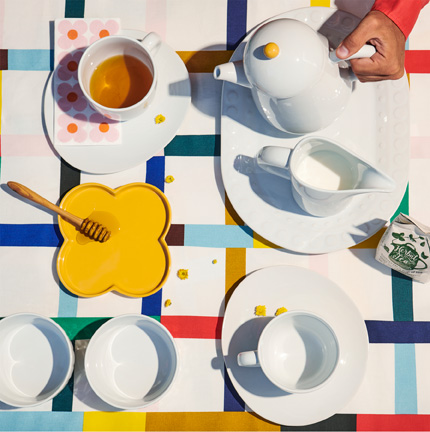 Top view of white tea cups, saucers and a teapot with a yellow honeycomb stand, on top of a colorful checkered tablecloth.