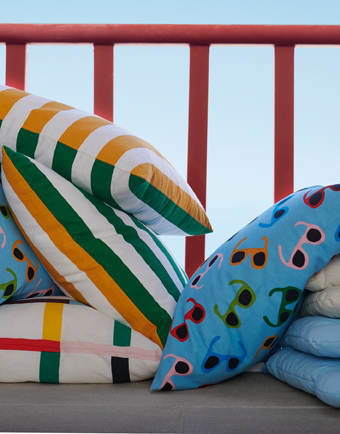 Several colorful cushions; including one light blue with sunglasses patterns, and some with orange and green stripes.