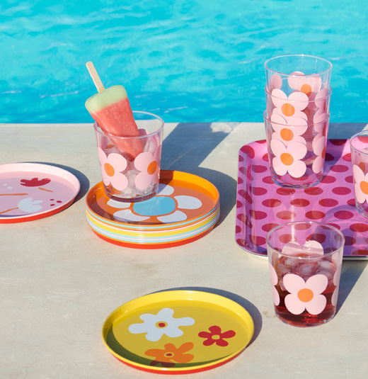 Summery tableware in front of water; including colorful plates and clear glasses with flowery prints.