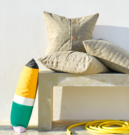 Three beige cushions on an outdoor bench and a yellow and green striped cushion next to the bench.