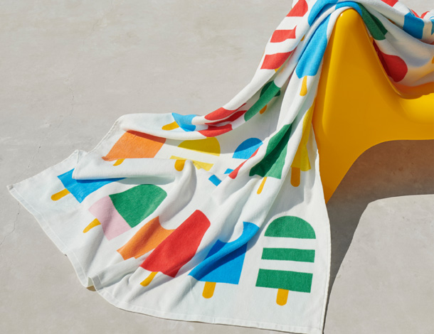 A white towel with colorful ice cream sticks draped over a yellow chair.