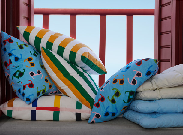 Several colorful cushions including light blue with sunglasses, green and yellow striped, and colorful checker pattern.