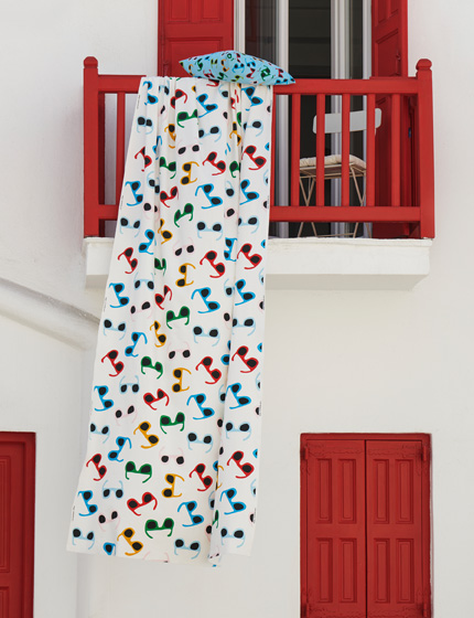 A white fabric with colorful sunglasses prints draped over a red balcony outdoor space.