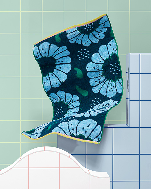Dry off in the retro floral pattern of SANDVILAN bath towel from IKEA. Shown against tiles, the towel has big, light blue flowers on a dark blue and green background. It's made of 100% cotton from more sustainable sources.