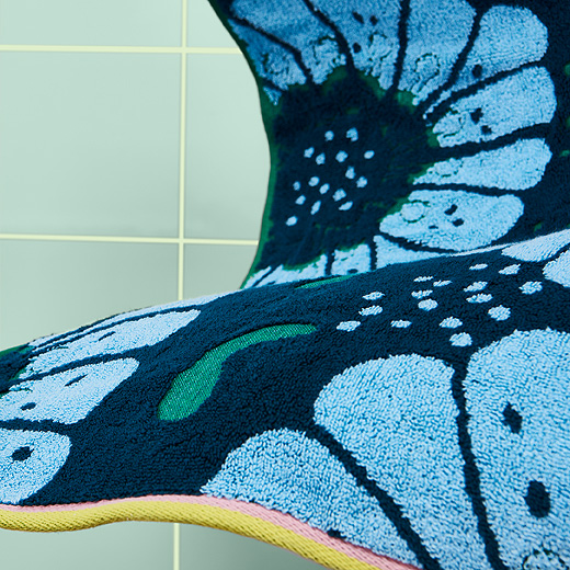 A close up of SANDVILAN bath towel from IKEA shows its jacquard-woven pattern of big, light blue flowers on a dark blue and green background. The 100% cotton towel's short edges have pink and yellow piping.