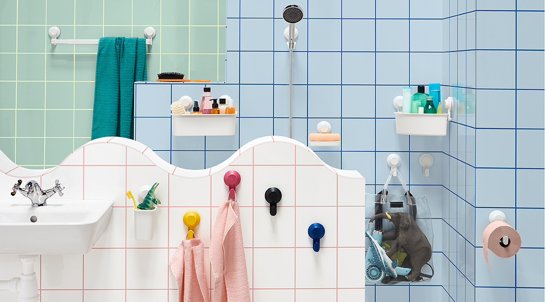 Hang towels in the bathroom using no-drill TISKEN towel rack with suction cup from IKEA. The extendable white rack holds up to 3 kg. It's shown on tiles with other TISKEN accessories like hooks and a basket.