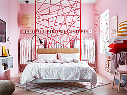 IKEA DELAKTIG is a customizable bedframe that is meant to be designed by you. This pink wall-to-wall bedroom proudly displays the sofa bed in the middle of the room with crisp white KUNGSBLOMMA bedsheets with red piping.