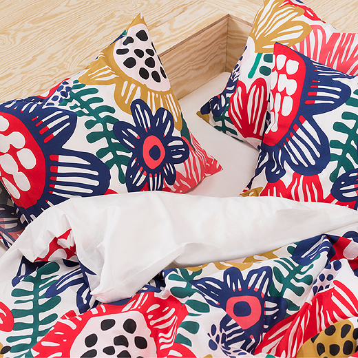 This IKEA SOMMARASTER quilt cover and two pillowcases close up shows its bright, retro floral pattern on 100% cotton. It has a white background seen through thickly drawn, airy petals in blue, yellow, red and pink.