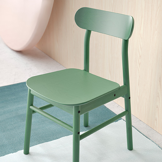A close-up of IKEA RÖNNINGE chair shows the entire dining chair with its rounded-shaped seat and angled back. It has a timeless Scandinavian design made in solid and layer-glued birch with a green tint.
