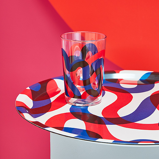 Serve up retro-inspired style with a FRAMKALLA tray from IKEA. A close up shows the circular melamine tray that has big, red and blue squiggles on a white background. A matching glass is shown on the tray.