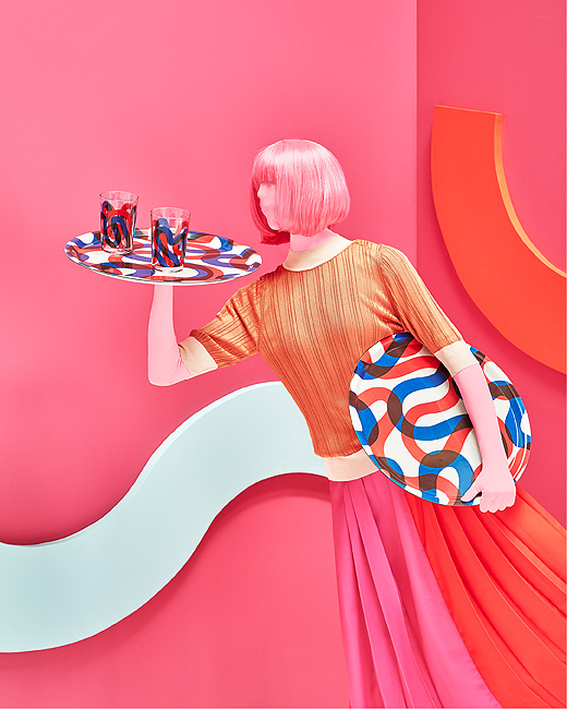 A mannequin with pink and orange clothing holding a blue and red serving tray with blue and red patterned glasses.