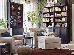 Two light beige IKEA GRÖNLID armchairs are in the living room with HAVSTA dark brown glass cabinets and open storage shelves for a modern style.