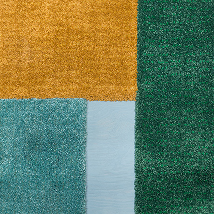 A close-up of IKEA LANGSTED low pile rugs in solid turquoise, yellow and green shows their cut edges. These edges allow you to cover a floor or place them side by side without worrying about visible seams.