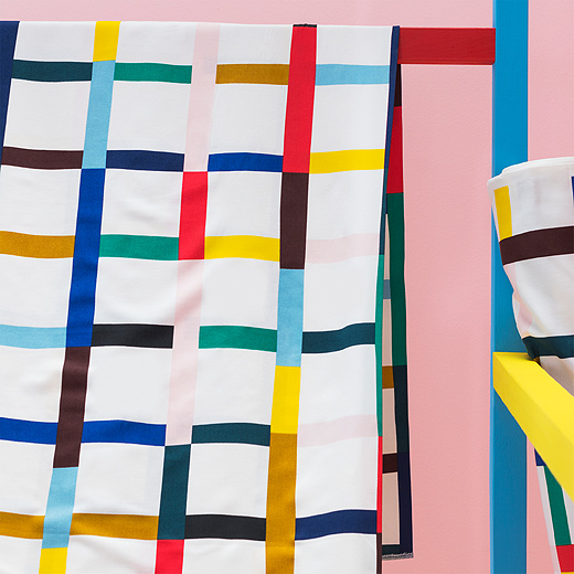 A close up of SIGRUNN metre fabric from IKEA shows its multicoloured grid pattern on a white background. Its vivid lines of red, blue, yellow, green, pink, brown and more vary in length for a striking effect.