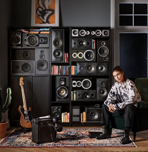 Black-brown bookcases used as shelving for several speaker systems, and a woman sitting on a chair with a guitar nearby.