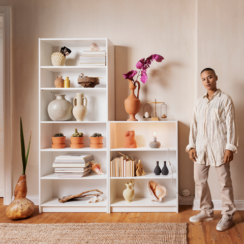 A man standing next to two different white bookcase heights with various decoration such as vases and plants.