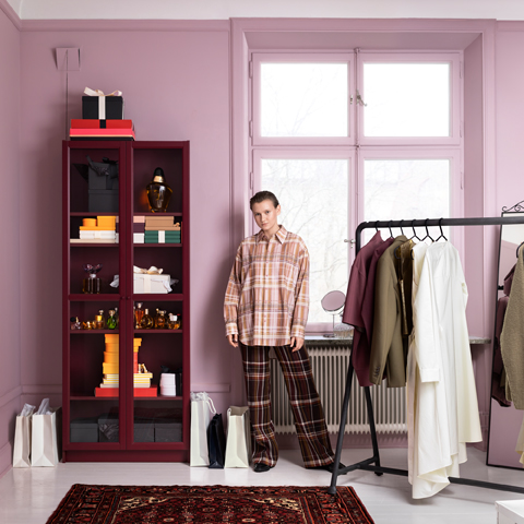 A person in a pink room next to a hanging clothes rack and a dark red bookcase with glass doors.