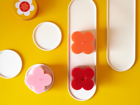 Top-down view of several round white candle dishes with pink, orange and red flowery candles sitting in them.