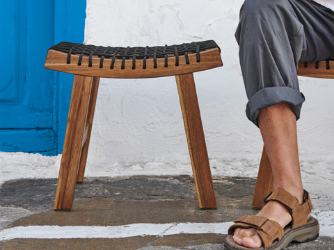Closeup of a wood acacia stool with a braided seat sitting outside next to a person's leg.