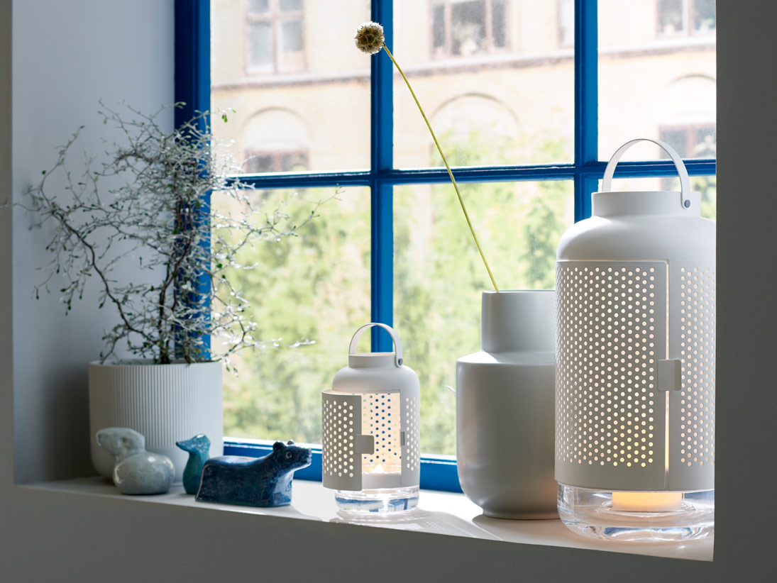 Two white lanterns on a window sill next to a vase with a single flower sticking out, and another plant nearby.