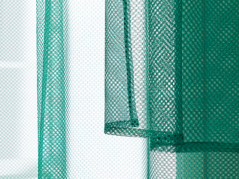 A close up of vivid green GRÅTISTEL net curtains from IKEA