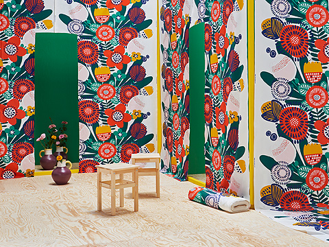 A room with several panels of fabric with colorful flower patterns, and two wooden stools.