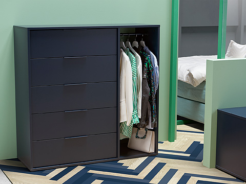 A dark blue chest of drawers with a compartment a clothes rail and hanging shirts, in a light green room.
