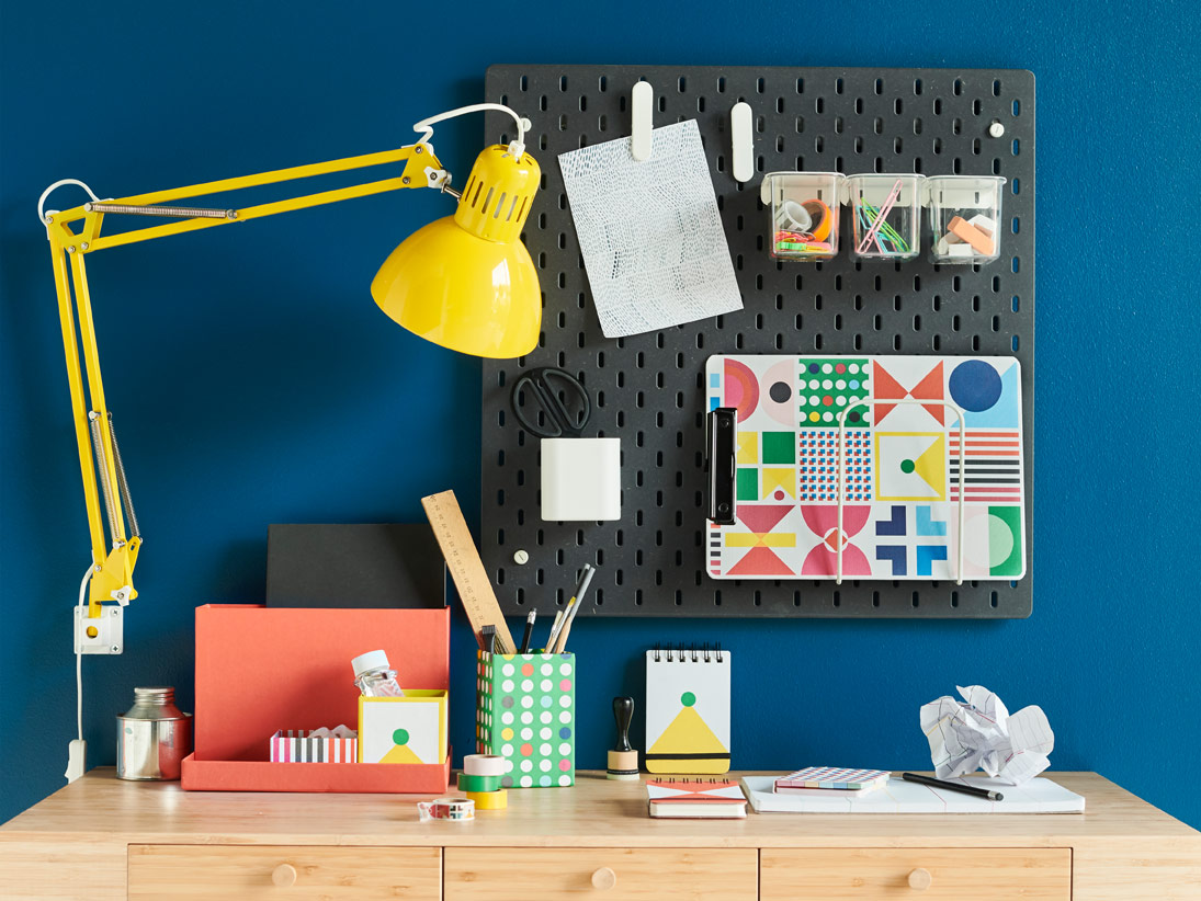 A black pegboard against the wall with several stationery items attached to it, above a cabinet with additional stationery.