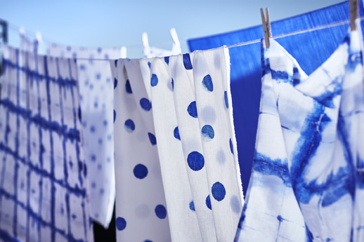The TÄNKVÄRD throw with blue dots on a white background, hanging on a laundry line with other textiles.