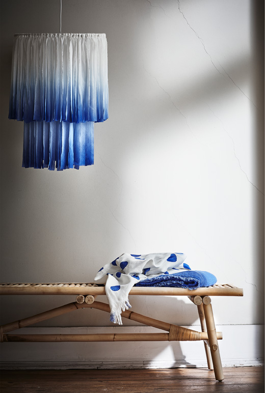 The TÄNKVÄRD lamp shade with indigo-colored fabric strips matches throws and rattan furniture.