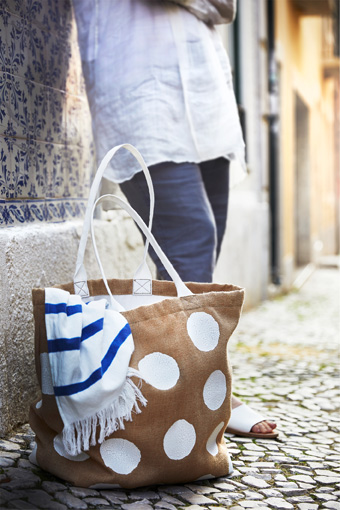 A TÄNKVÄRD jute bag in natural colour and white dots, together with a spa towel from the same collection.