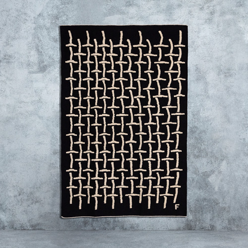 A black large handwoven rug with a white grid pattern, designed by Filip Pagowski for IKEA ART EVENT 2019.