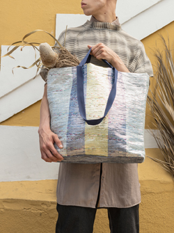 A yellow, turquoise and blue ÖVERALLT bag made from crisps packaging waste.