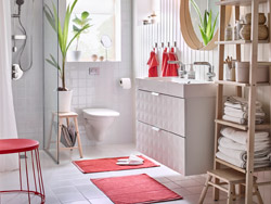 A white and red color-schemed bathroom with a white double sink and wooden shelving next to it.