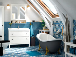 A white sink cabinet against a blue tile wall with a nearby clawfoot tub.
