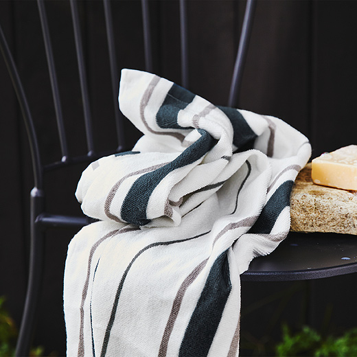 A close-up of a white OTTSJÖN towel shows its vertical grey and blue stripes made of 100% sustainably sourced cotton.
