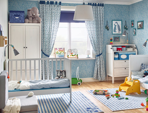 This twin's calm, blue baby bedroom includes two IKEA SUNDVIK white cots with traditional wood finishes along with a SUNDVIK changing table with two closed drawers and one open storage shelf below the table surface.