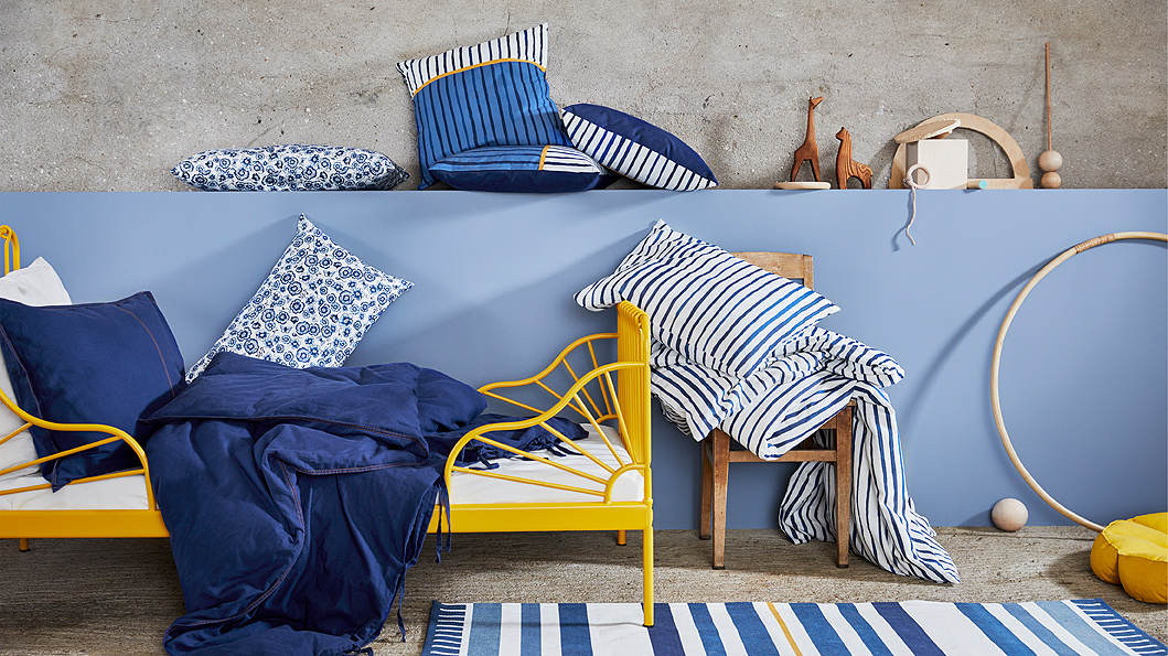 Shown by a kid's bed is the blue-and-white SÅNGLÄRKA textile collection of cushions and a quilt cover in stripes and florals.