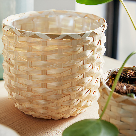 A close-up of a KAFFEBÖNA plant pot shows the unique variations of its light blonde, handwoven bamboo strips.