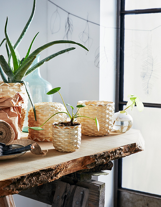 Accent your plants with the blonde bamboo of handwoven KAFFEBÖNA plant pots in round sizes shown on a planting bench.