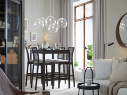 A dark gray bar table with four bar stools in a dining room with a white sofa in a nearby living room.