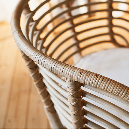 A close-up of BUSKBO armchair shows its airy, curved backrest with horizontal rattan supports and a wrapped top piece.