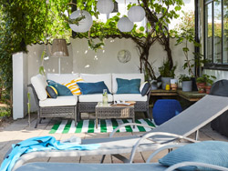 Outdoor seating furniture series coupled with bright bath towels, plants and paper lanterns.