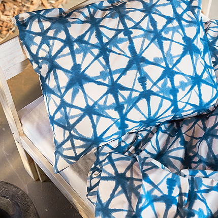 A close-up of 100% cotton STJÄRNFLOCKA quilt cover and pillowcase shows its starry, triangular pattern in blue on white.