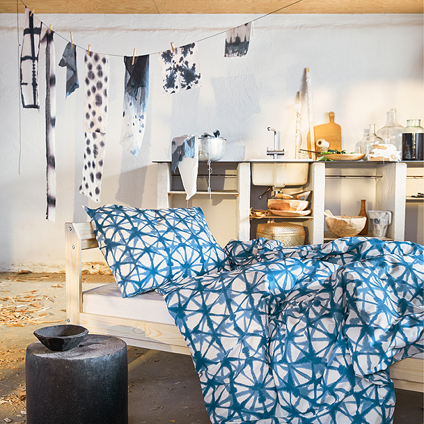 An artsy bedroom shows a bed with the blue-on-white STJÄRNFLOCKA quilt cover made to look like a Japanese dyeing technique.