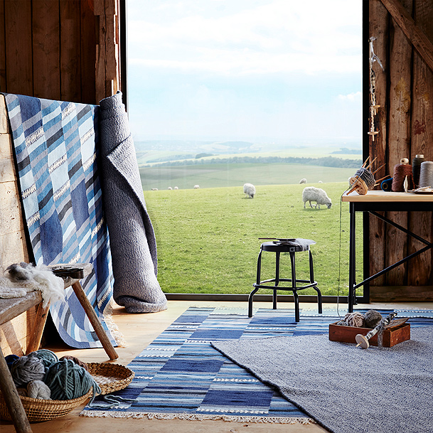 LOVRUP wool and 20% cotton rugs and TRANGET wool rugs in shades of blue are shown on a floor and against a wall in a barn.