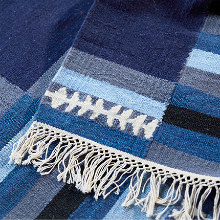 A close-up of TRANGET rug shows its white fringe and handwoven wool rectangular patch pattern in various shades of blue.